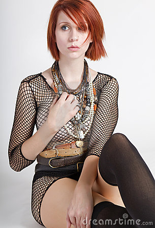 Beautiful young redhead female wearing fishnet top