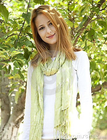 Beautiful young redhead woman near the apple tree