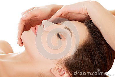 Beautiful young relaxed woman enjoy receiving face massage at sp