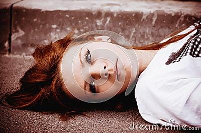 Beautiful young sad girl lying on asphalt
