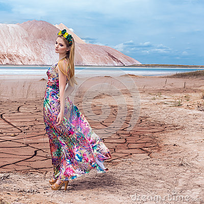 Free Beautiful Young Sexy Girl Model With Long Red Hair In A Beautiful Wreath Of Flowers And A Long Bright Colored Dress In The Desert Stock Photos - 56841293