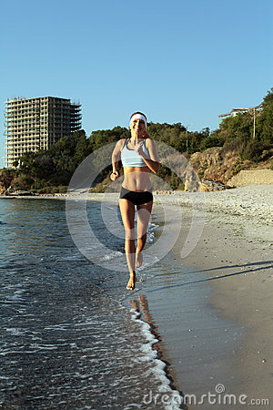 Beautiful young sport woman running on beach