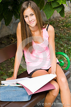 Beautiful young student girl studying outdoors.