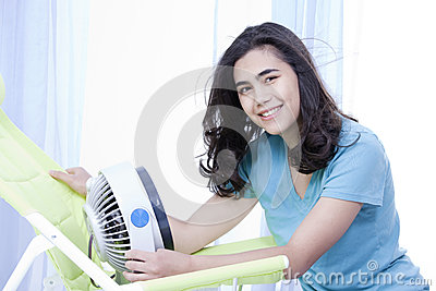 Beautiful young teen enjoying cool fan breeze