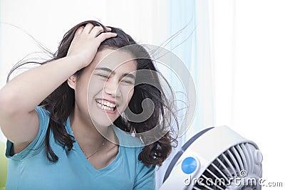 Beautiful young teen enjoying cool fan breeze