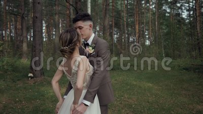 Beautiful young wedding couple in beautiful forest. Hugs, kisses and smiles.  stock video