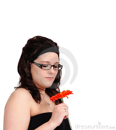 Beautiful young woman admiring a flower closeup