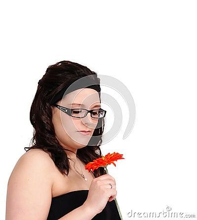 Beautiful young woman admiring a flower closeup