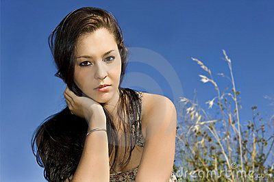 Beautiful young woman against blue sky