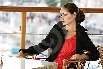 Beautiful young woman alone in street cafe