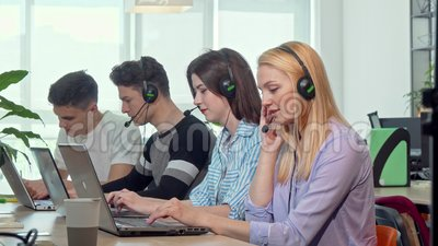 Beautiful young woman answering calls, working at customer support call center. Young people working at technical support service, wearing headsets with stock video footage