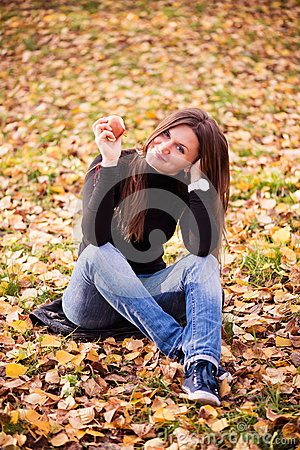 Beautiful young woman with apple in autumn park