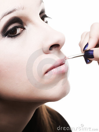 Beautiful young woman applying lips make-up zone