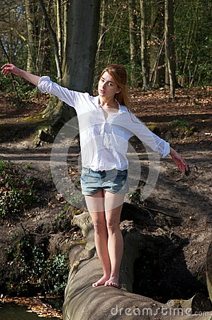 Beautiful young woman balancing on a log across a stream