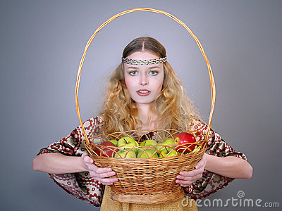Beautiful young woman with a basket of apples