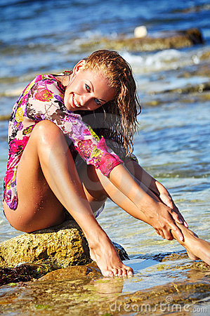 The beautiful young woman on a beach in a wet dres