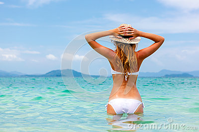 Beautiful young woman in bikini on the sunny tropical beach