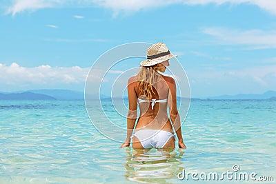 Beautiful young woman in bikini on the sunny tropical beach