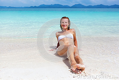 Beautiful young woman in bikini on the sunny tropical beach rela