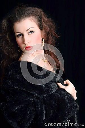 Beautiful young woman in black fur