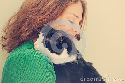 Beautiful young woman with black and white cat