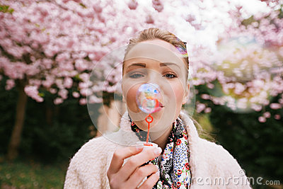 Beautiful young woman blowing bubbles at park