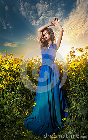 Beautiful young woman in blue dress posing outdoor with cloudy dramatic sky in background