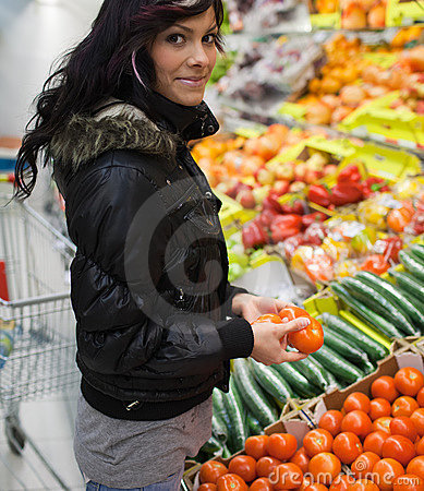 Beautiful young woman buying vegetables