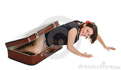 Beautiful young woman climbing out of suitcase