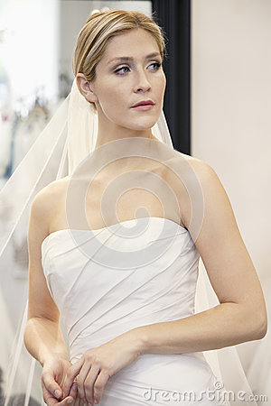 Beautiful young woman dressed up in wedding gown looking away