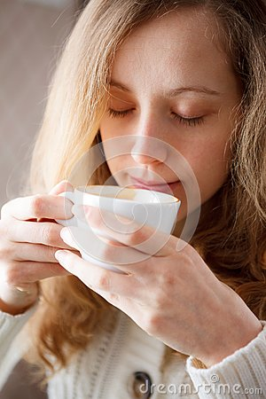 Beautiful young woman drinking coffee. Cup of hot beverage