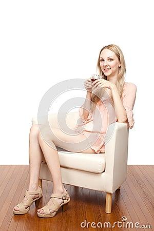 Beautiful young woman drinking tea sitting