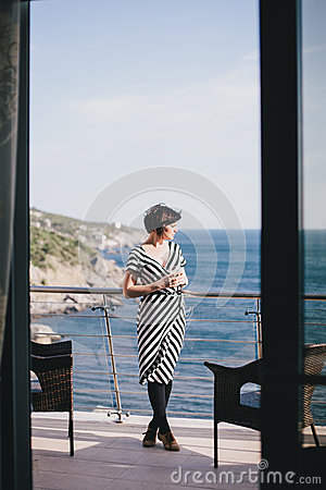 Free Beautiful Young Woman Drinking Wine And Standing On A Balcony With Beautiful Ocean View Stock Photos - 54834063