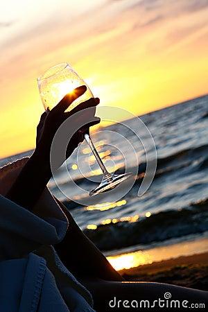 Beautiful young woman drinking wine on beach