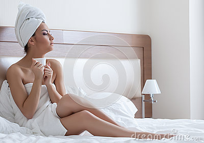Beautiful young woman drinks coffee after shower