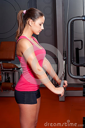 Beautiful young woman exercising arm muscles