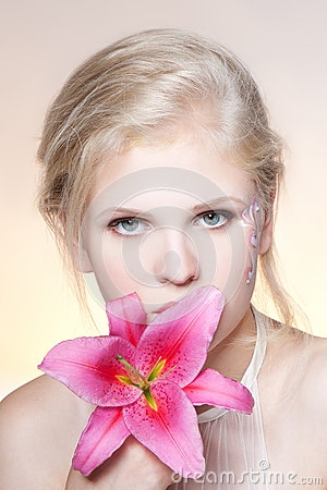 Beautiful young woman face with fresh flower