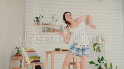Beautiful young woman feeling happy, jumping and dancing. Brunette girl in pajamas having fun in morning at home. Female enjoying the day stock video footage