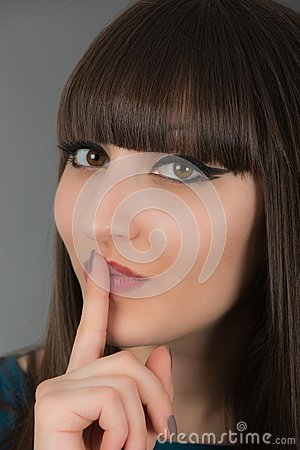 Beautiful young woman gesturing for silence by holding a finger