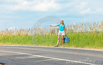 Beautiful young woman hitch hiking- in auto-stop