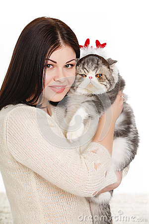 Beautiful young woman holding a cat, isolated against white background
