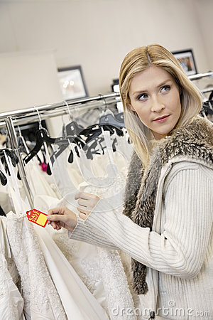 Beautiful young woman holding price tag while looking away in bridal store