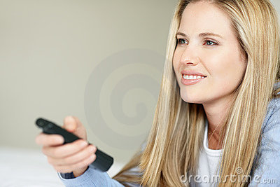 Beautiful young woman holding TV remote control