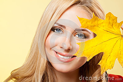 Beautiful young  woman holds maple leaf