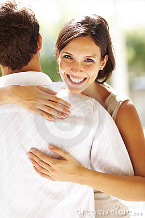 Beautiful young woman hugging a man and smiling