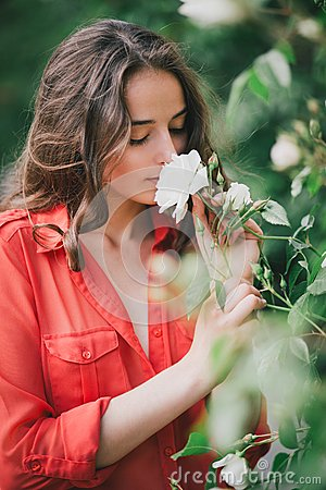 Free Beautiful Young Woman In A Red Shirt Smelling A Rose Stock Images - 40896914