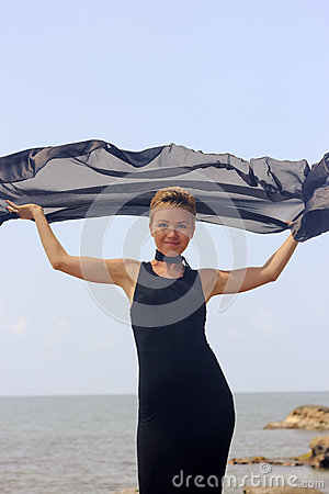 Free Beautiful Young Woman In Black Evening Dress Holding Black Fabric At Wind At The Seaside Stock Images - 52653434