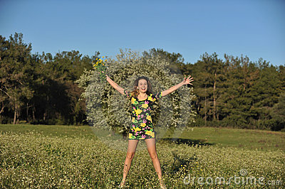 Beautiful young woman jumping in blooming meadow