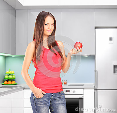 Beautiful young woman in a kitchen, holding an apple