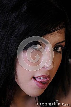 Beautiful young woman licking lips